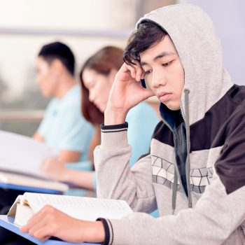 Close-up image of a tired student in the hood at the lesson on the foreground